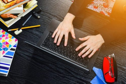 Image of hands using a laptop with books stacked on the desk