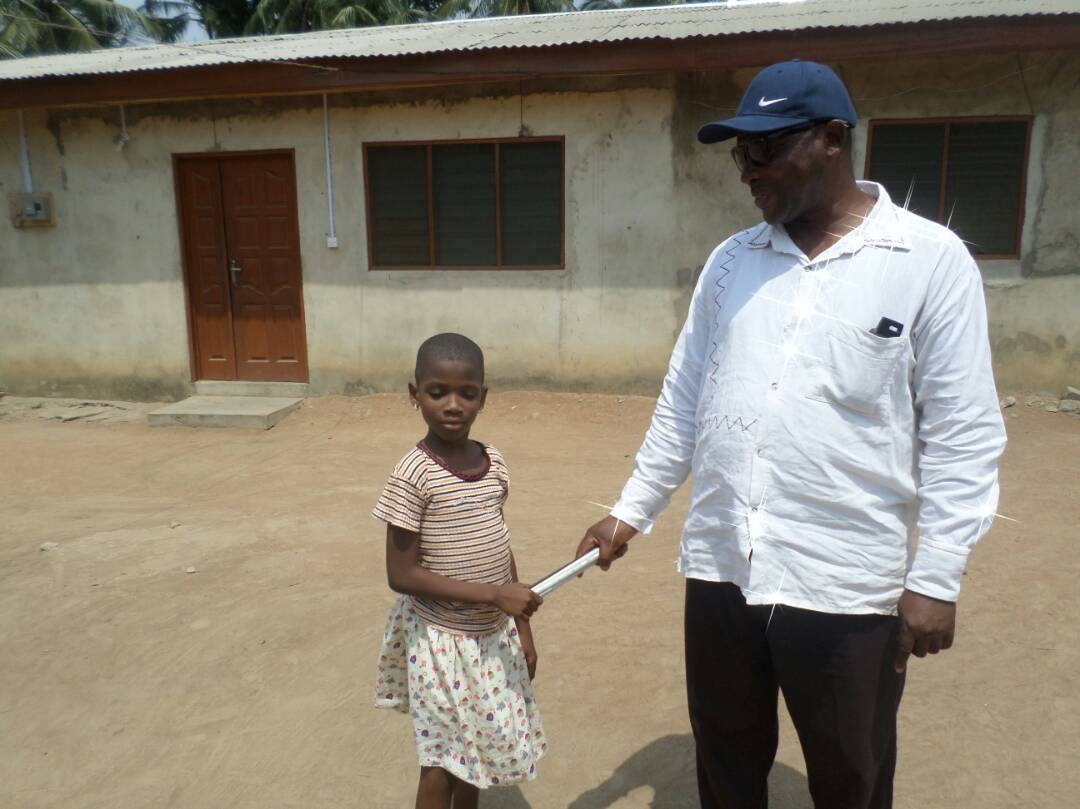 Photo shows little Ghanian girl holding a long cane, donated by the NCBI and assisted by her teacher