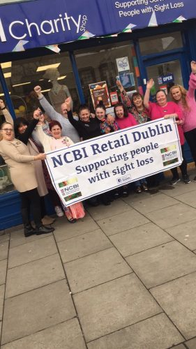 Photo of Tracey, staff and volunteers outise the NCBI shop in Crumlin .They are holding a large banner saying NCBI Retail Dublin