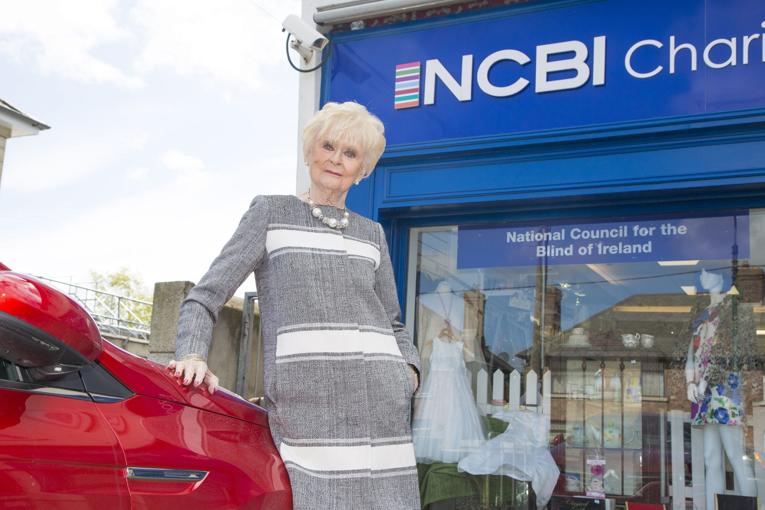 Photo of Rosemary Smith wearing a beautiful coat pictured modelling outside the NCBI shop
