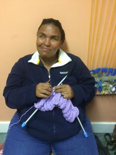Image is of a smiling Sharon Byrne as she knits a garment