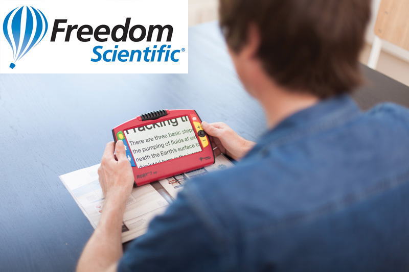 freedom scientific logo with a photo of a guy using a RUBY handheld video magnifie