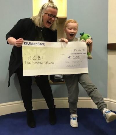 Josh (age 7) and Sarah from our Fundraising team, holding up a large cheque for €500. A special blue Teddy bear named Scout is helping too. Sarah and Josh are smiling with their mouths open, making reference to their 'socks'