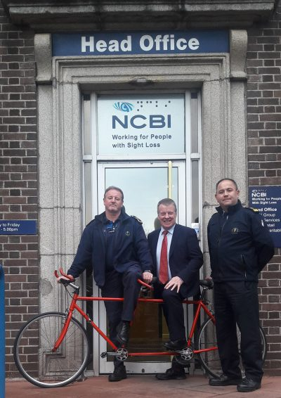 *image of Greg (Arbour Hill), Joe McKenna (NCBI) and Dave Walsh (Arbour Hill) with the donated red tandem bicycle