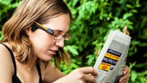 Image of a woman wearing the OrCam reading a newspaper