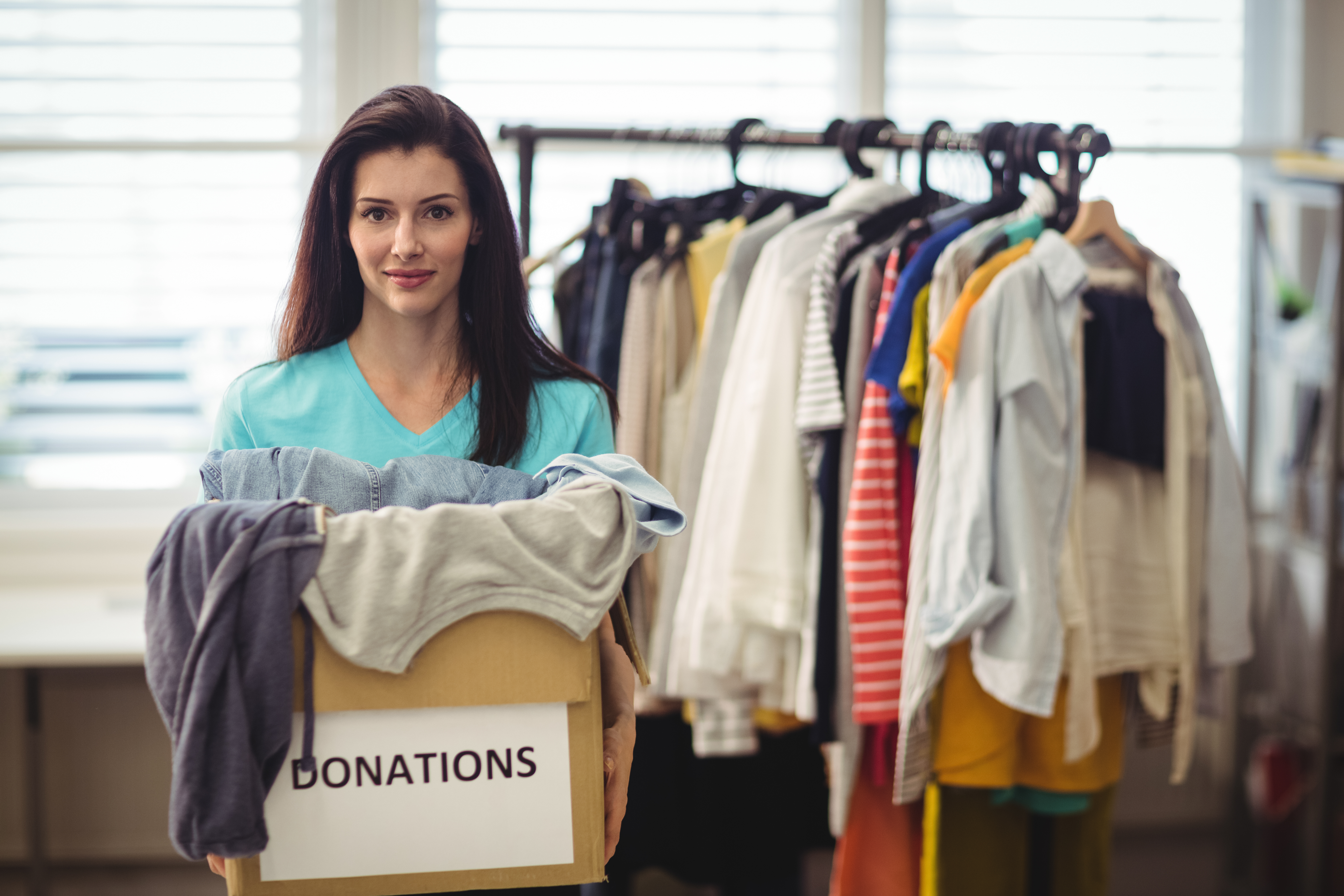 Female volunteer holding clothes in donation box at workshop