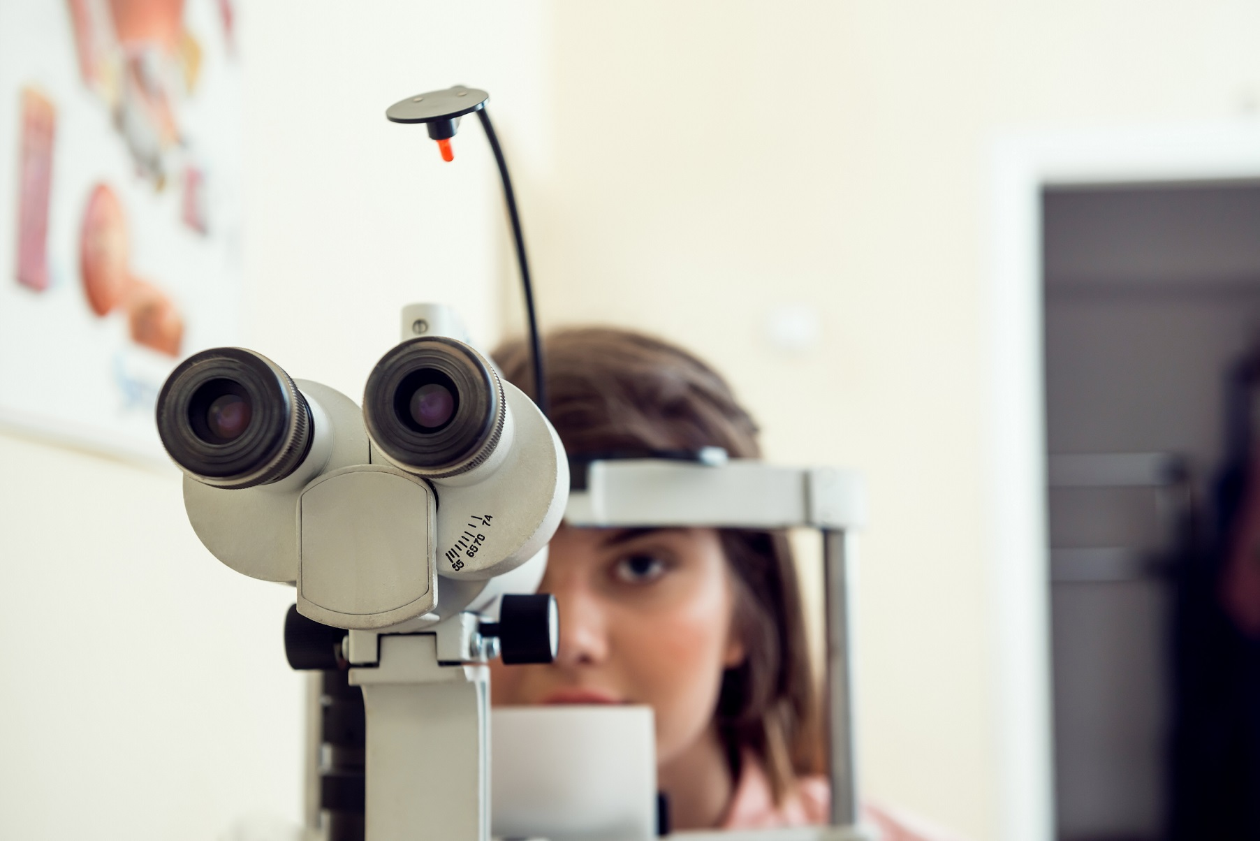 Portrait female patient sitting in optometrist office, waiting for start of procedure to check her vision with microbioscope,