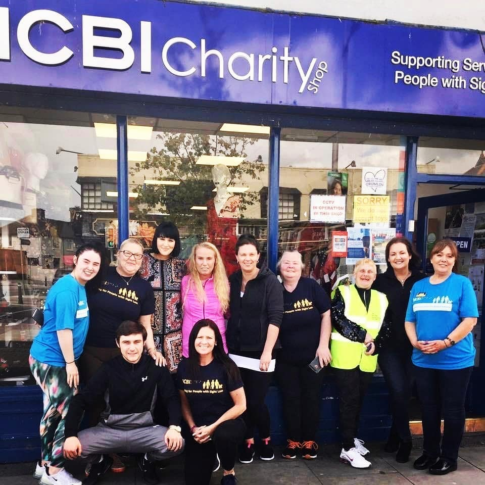 Group of NCBI volunteers in front of one of NCBI charity shop