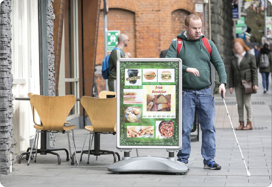 man walking with cane into outdoor food sign