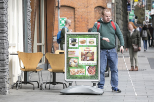 a blind man with his white cane walking on the footpath run into sandwich board