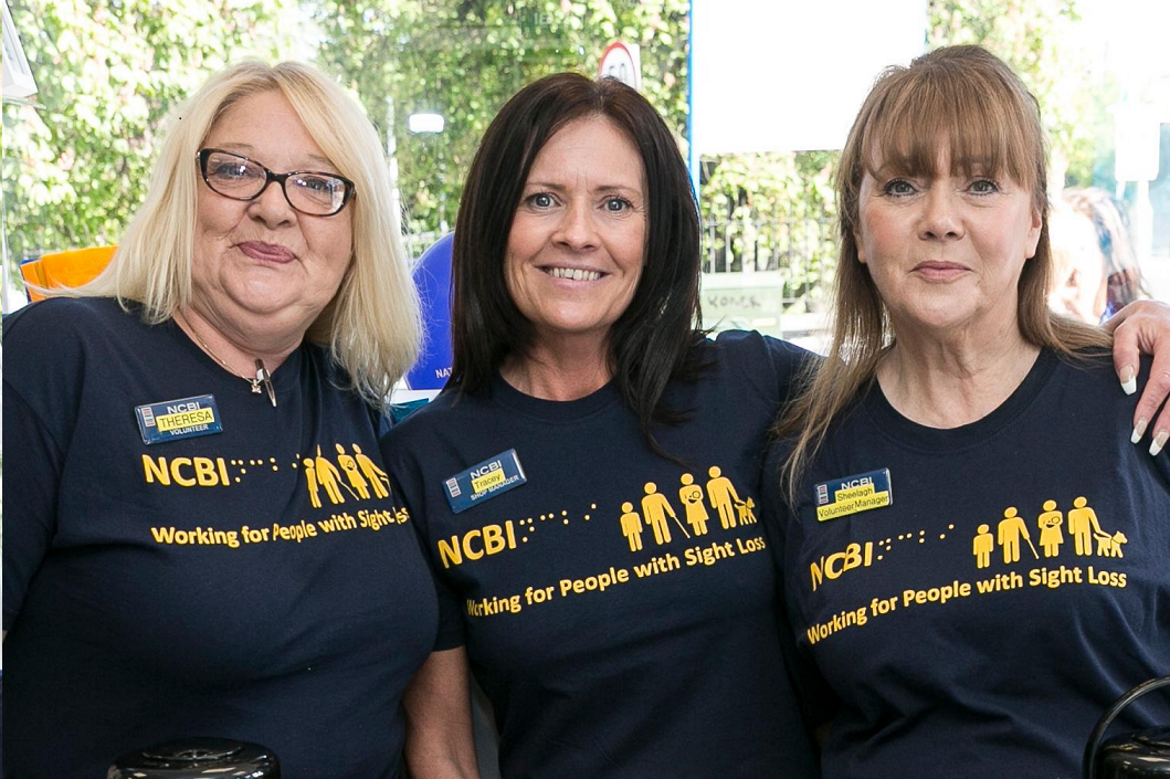 Photo of three middle age women wearing a dark blue NCBI t-shirt