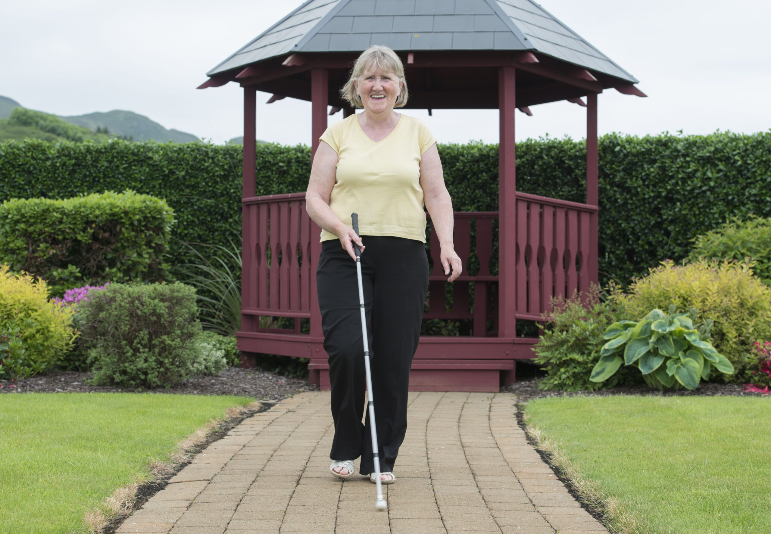 Image of Margaret walking with her cane