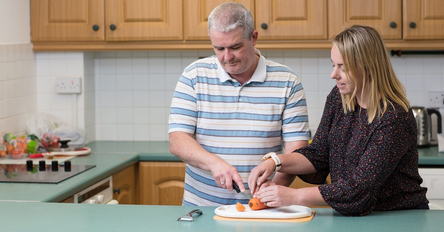 A blind man being guided how to cut carrots.