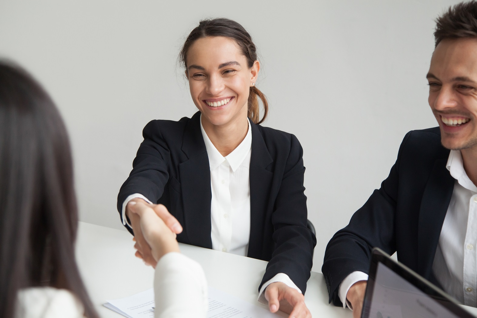 Smiling female hand-shaking her employer