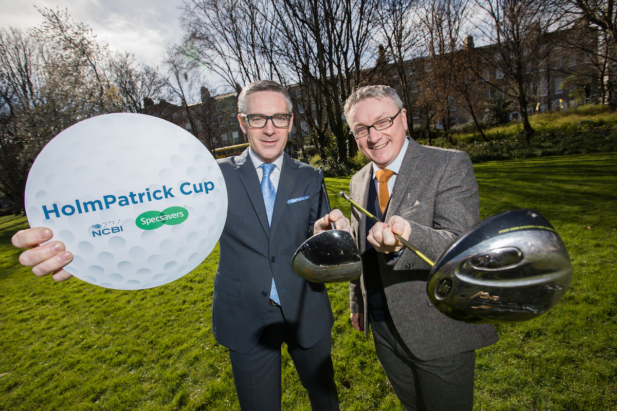Photo of two man, the one in the left is holding a sign written HolmPatrick Cup and the other is holding a golf club