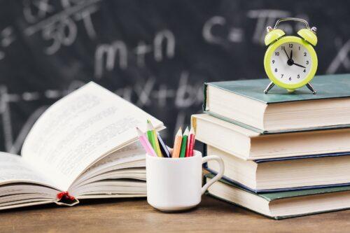 clock on top of books at teacher desk
