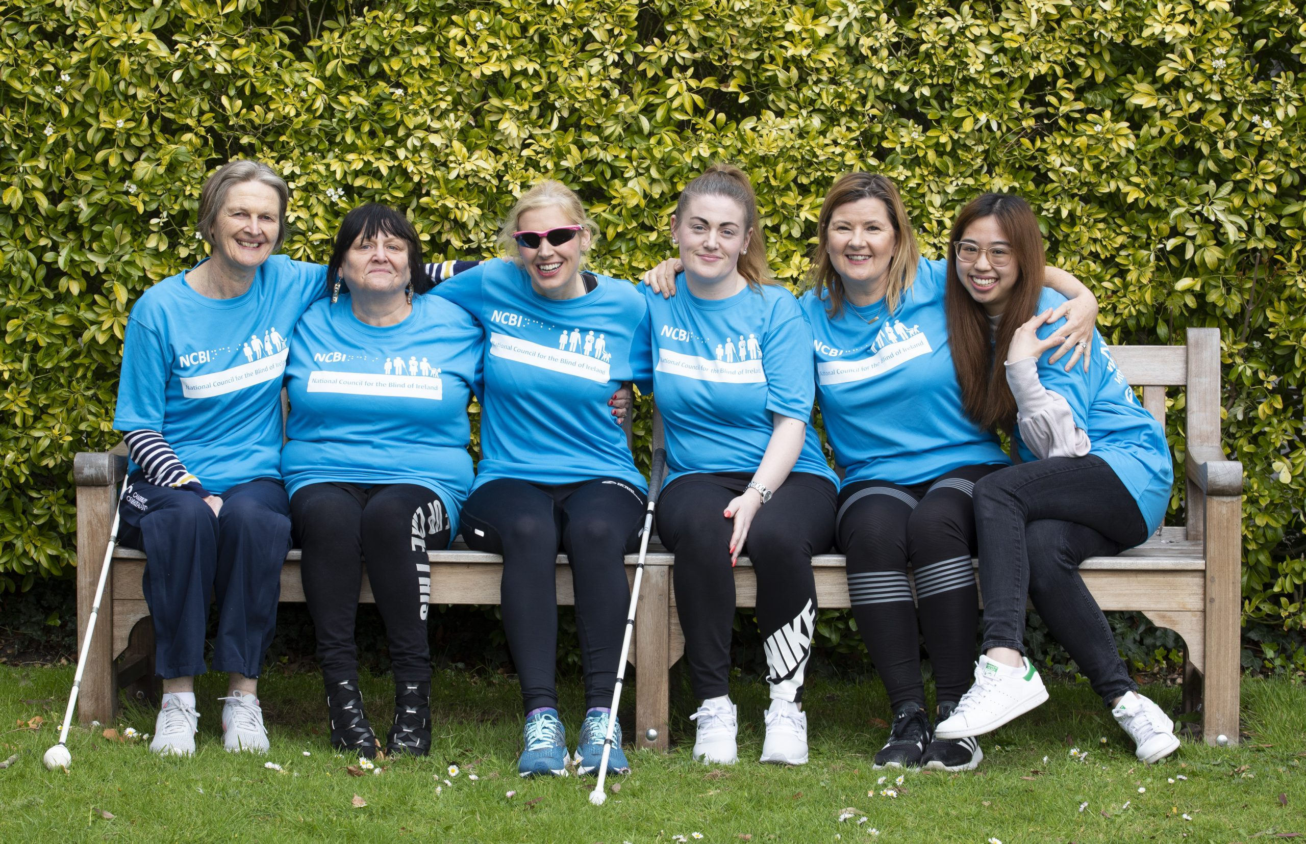 Various NCBI team members in light blue running tops gather around Dr Sinead Kane on a sunny park bench and hold light-hearted stretch poses for the camera.