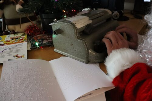 Photo os NCBI Santa writing a letter in braille