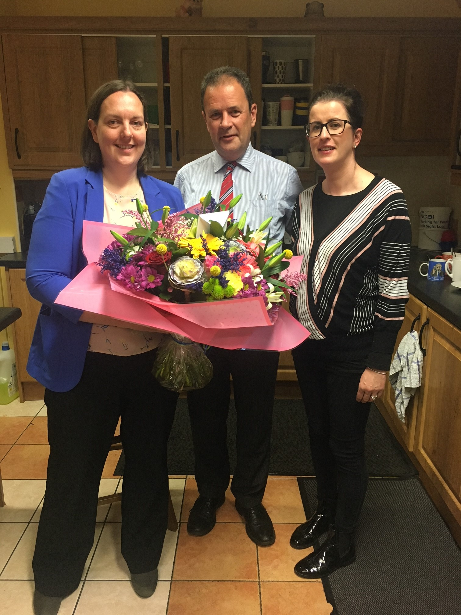 Image of Fionnuala, Ruairi and Niamh Connolly with flowers