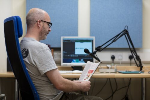Photo of a man being recorded reading a book