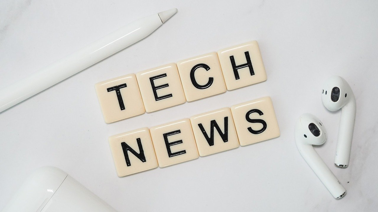 Tech News compiled in scrabble pieces next to set of white ear pods