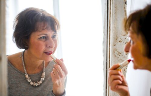A lady in her 60s putting on lipstick in a mirror