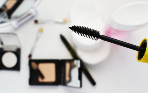 A mascara wand being held up with makeup on the table blurred out