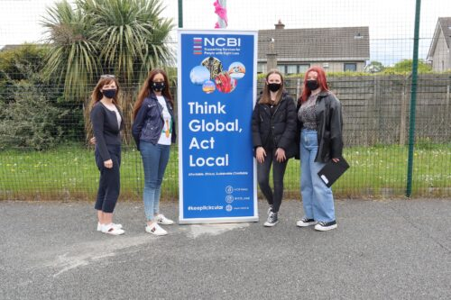 4 woman stading in front of a pop up saying Think Global Act Local