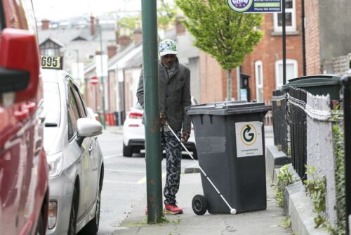 Photo of a man using his long and a bin cane is blocking his way