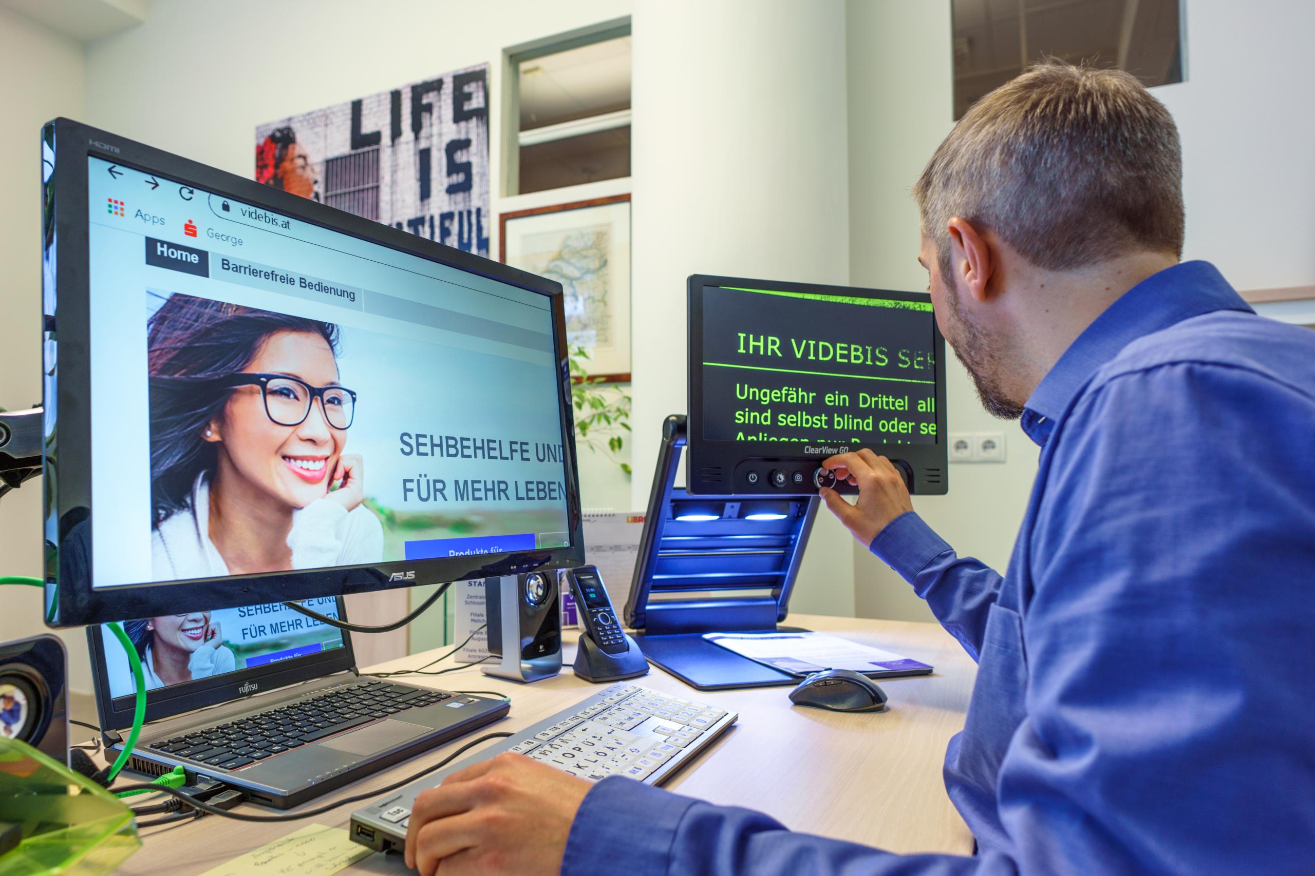 Man sitting at desk using computer and CCTV