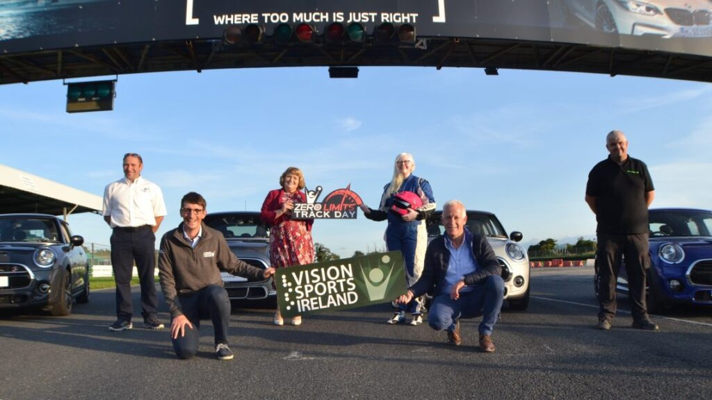 Staff pictured in front of cars holding Vision Sports banner